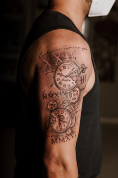 Side view of crop anonymous fit male demonstrating forearm with tattoo representing round clocks with Arabic numerals and Latin numbers surrounded by letters