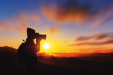 Woman tourists taking pictures on a mountain against the background of sunrise in the morning.