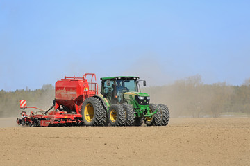 John Deere Tractor and Seed Drill on Dusty Field. Illustrative Editorial content.
