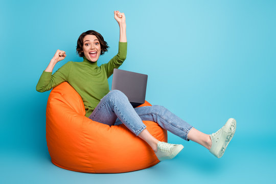 Full length photo of amazed crazy girl sit bean chair use laptop celebrate win raise fists scream wear green sweater denim jeans isolated over blue color background