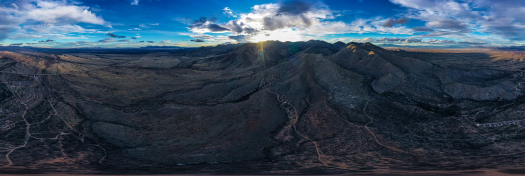 Aerial view and panorama of Arizona mountain ranges during sunset with clouds and sun