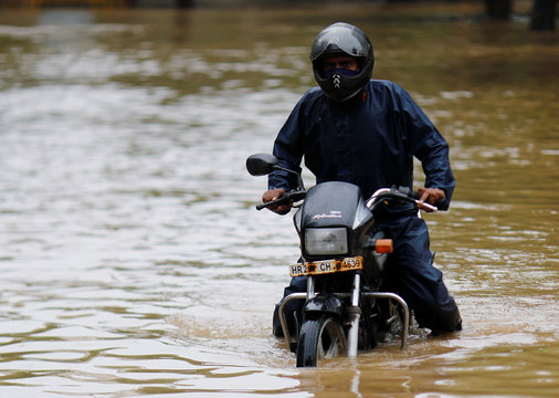 A man got stuck on his bike in a flooded street after heavy rains in Gurugram