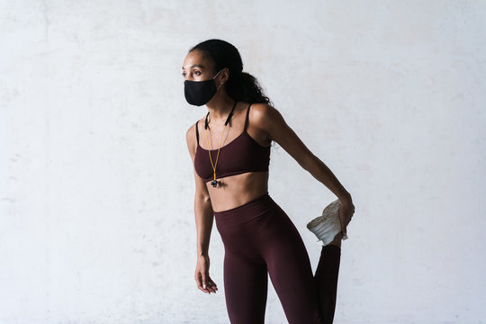 Photo of athletic african american woman in face mask doing exercise