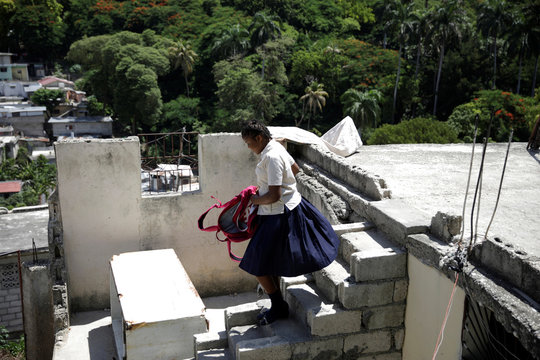 Nickerla Ambroise Etienne walks while carrying a backpack outside her house in Port-au-Prince