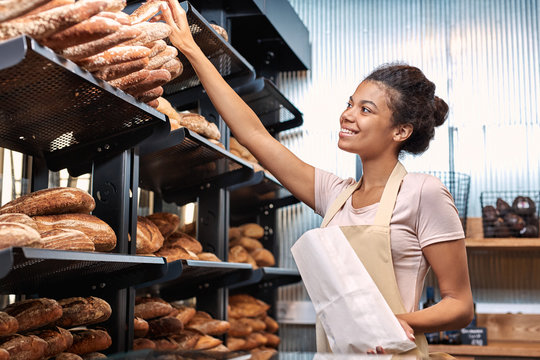 Small Business. Young woman in apron at bakery shop taking baguette from shelf putting into paper bag smiling happy