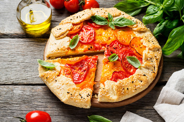 Delicious homemade rustic open pie (galette) with colorful tomatoes and basil leaves .