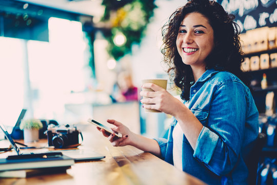 Half length portrait of smiling hipster girl with curly hair laughing while having working break indoors.Cheerful cute student having fun while recreating indoors.Happy woman looking at camera