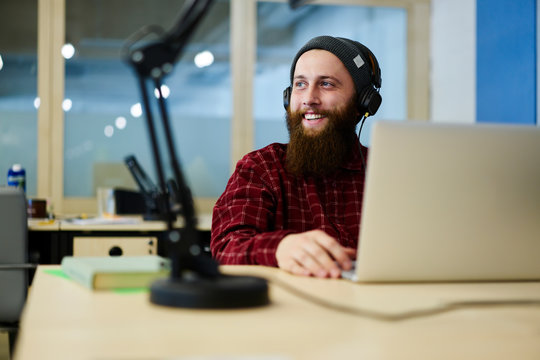 Cheerful graphic designer enjoying favorite compositions playing over cool headphones during work break.Bearded smiling copywriter listening good music while looking away sitting in office