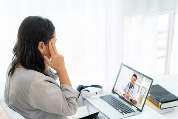 Asian woman in white bed speaking with doctor using tele health technology while sitting on a sofa and headache in bedroom at home while she sick during self quarantine for COVID-19.