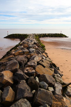 A row of sea defence boulders jutting out into the water.