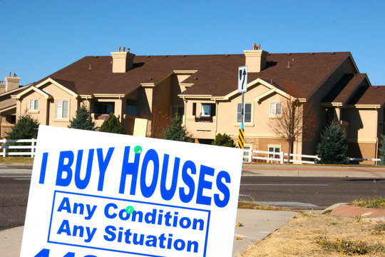 Sign stating: I Buy Houses, Any Condition, Any Situation on a street corner, in a suburban development. An opportunist is taking advantage of people trying to avoid foreclosure in the mortgage crisis.