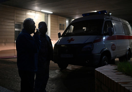 Men stand next to an ambulance outside a hospital where Russian opposition leader Navalny was admitted, in Omsk