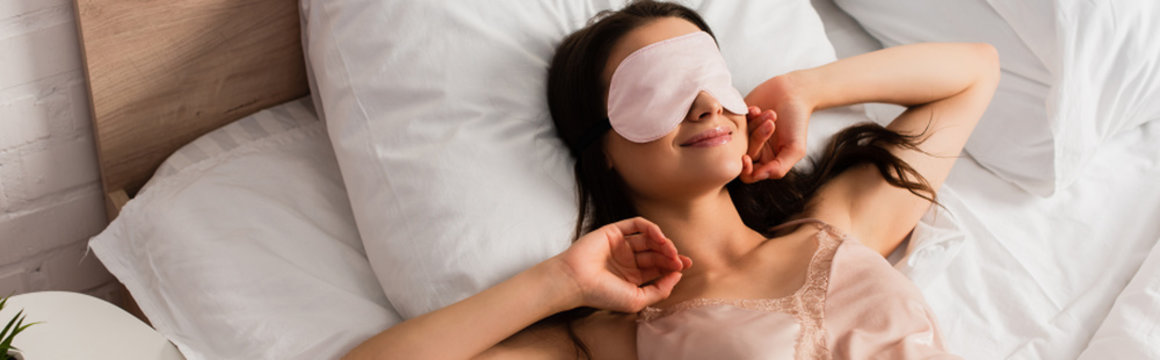 panoramic concept of young woman in eye mask lying on bed