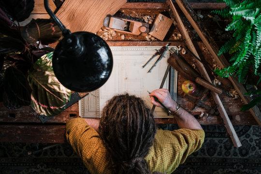 Mann mit Dreadlocks zeichnet auf Werkbank umgeben von Pflanzen und Werkzeug - von oben aufgenommen
