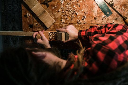 Mann mit Dreadlocks in rotem Hemd hobelt ein Stück Holz von oben aufgenommen