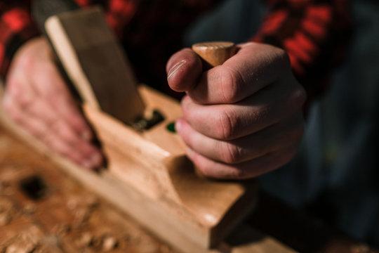 Hand hält Hobel während des hobelns eines Stück Holzes