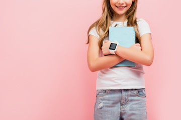 cropped view of girl in smartwatch holding book isolated on pink