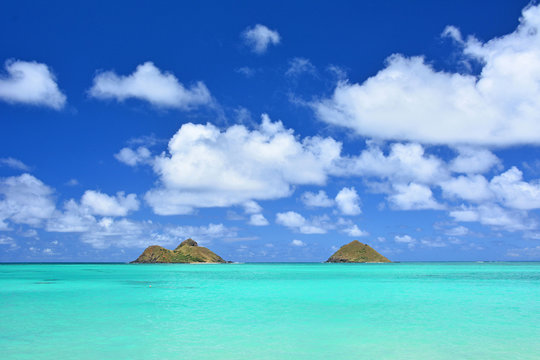 Tropical Hawaiian beach with clouds, blue skies, and a picturesque view of Mokuluas at Lanikai in Kailua, Oahu