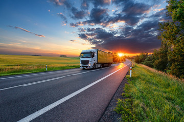 Fotobehang - Truck driving on the asphalt road in rural landscape in the rays of the sunset with dark storm cloud