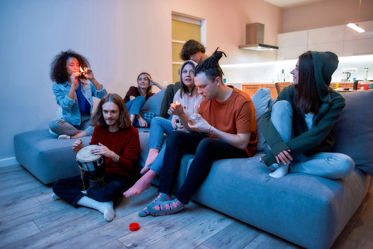 Young guy lighting marijuana in the glass bong and smoking it, relaxing with friends on the sofa at home, young people smoking weed together