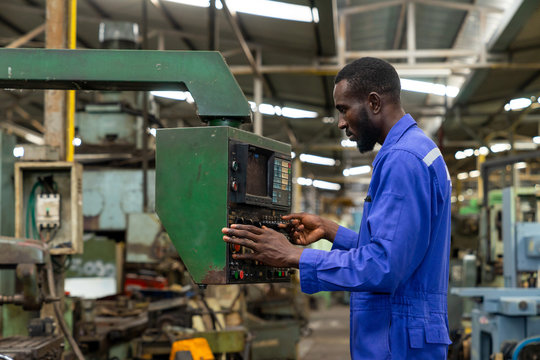 African american industry worker control machines in the workplace on a business day.  Technician engineer checking and working in the factory. Concept of Industrial manufacturing.