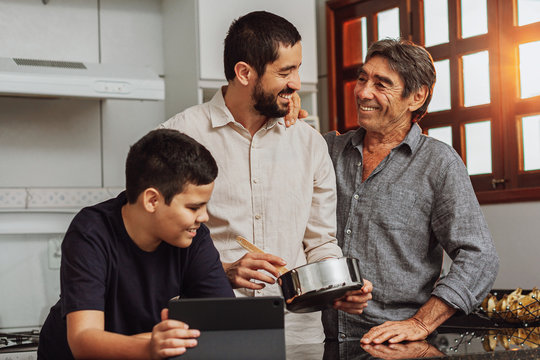 Male members of three generation family enjoying the day together in home cooking in the kitchen