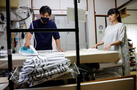 Japanese artist Hiroko Takahashi talks to Kimono tailor Kazumi Furuoya as he works on a fabric she designed, at Furuoya's studio, in Tokyo