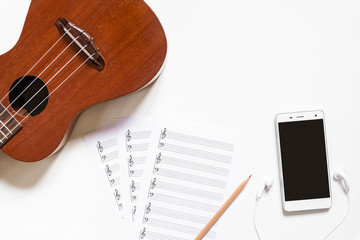 Top view of ukulele with blank stave pad bar for music notes and smartphone