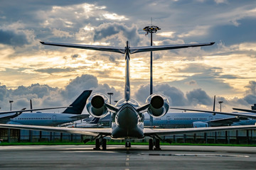 Private business jet parking at parking stand under sunset