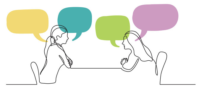 two young women sitting behind table talking with speech bubbles