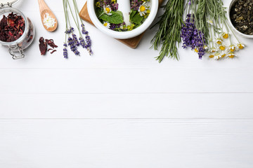 Flat lay composition with healing herbs on white wooden table. Space for text