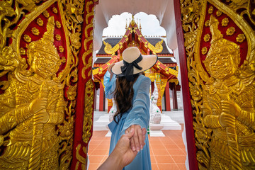 Wall Mural - Woman holding man's hand and leading him to Wat Khua Khrae in Chiang rai, Thailand.