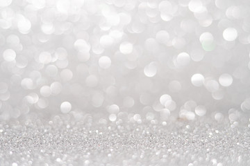 silver Sparkling Lights Festive background with texture. Abstract Christmas twinkled bright bokeh...