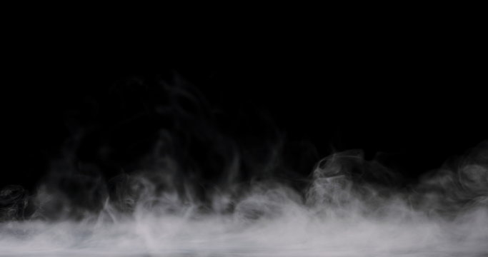 white fog rolling across the ground against a black background and staying low.