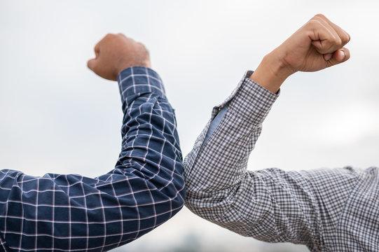 Two businessmen Shaking elbows keeping social distancing.