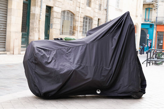 motorbike protected by plastic cover in street motorcycle with tarpaulin jacket