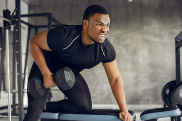 Sports man in the gym. A black man performs exercises. Guy in a black t-shirt