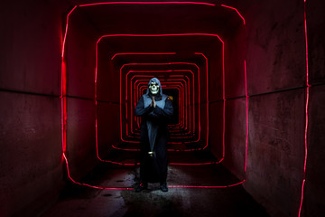 Shot of a person dressed as the grim reaper in a tunnel with red lights