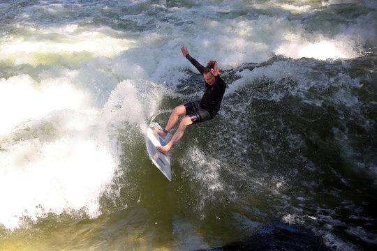 A surfer catches a wave in the freezing water of the Eisbach River in the Munich's famous English Garden, in Munich