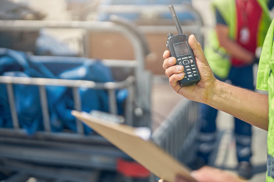 Man holding a walkie-talkie and a clipboard