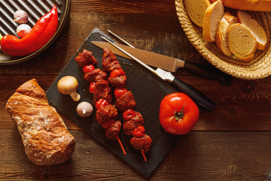 bbq skewer with beef tomato on slate plate with garlic mushroom meat knife and fork bread in basked red chilli pepper in cast-iron grill pan