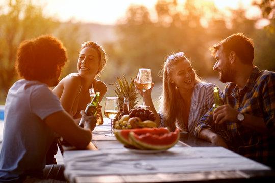 friends having fun outdoor, talking and laughing enjoying at evening.