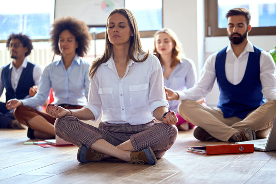 Young colleagues having yoga in the office; Mindfullnes in the office concept