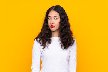 Mixed race woman over isolated yellow background standing and looking to the side Fotomurales