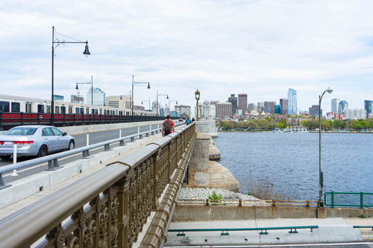 Transportation background with the Boston Skyline in the background showing cars, MBTA trains, people, and the Charles River.