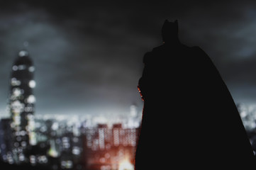 NEW YORK USA, AUGUST 21 2020: Batman from DC Comics looming over Gotham City at night - Mattel action figure