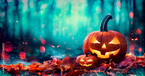 Jack O' Lanterns On Red Leaves In Spooky Forest With Defocused Ghosts