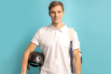 portrait of young caucasian sportive man with helmet for bike looking at camera and smile, wearing...