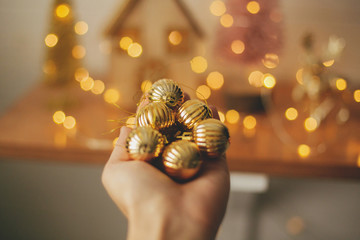 Hand holding modern gold baubles on background blurred illumination lights. Decorating christmas...