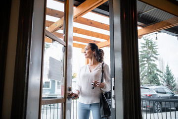 Female business owner opening cafe door